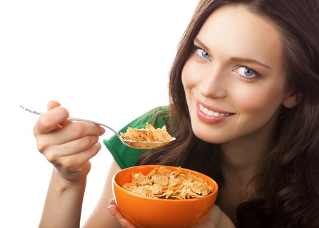 cereal bowl: Portrait of young smiling woman eating muesli or cornflakes, isolated on white background Stock Photo