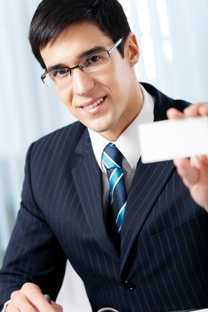 Smiling businessman giving business card, at office photo