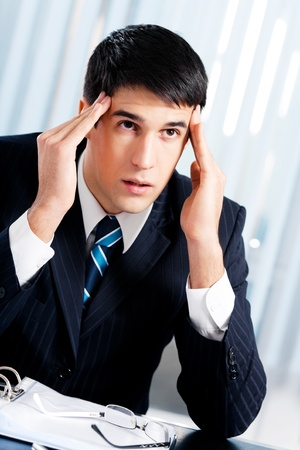Thinking, tired or ill with headache businessman at office photo
