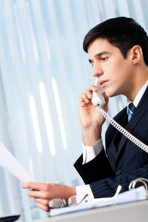 Successful businessman with phone and document at office photo