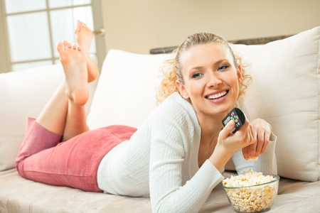 woman watching tv: Young happy smiling woman watching TV and eating popcorn at home Stock Photo