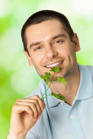 potherbs: Atractivo feliz sonriente joven con potherbs, al aire libre Foto de archivo