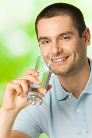 1 man only: Young happy smiling man drinking water, outdoors