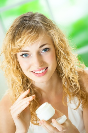 Young beautiful smiling woman with creme, at home photo