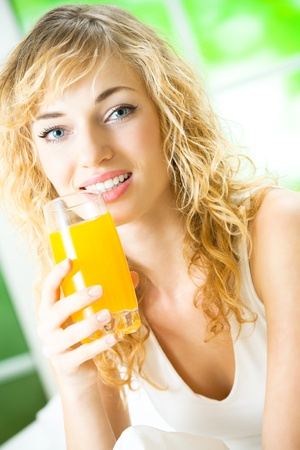 Portrait of happy smiling young woman with juice of tropical fruit at home photo