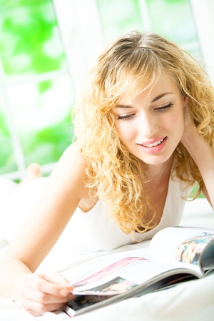 Young smiling woman reading magazine at home photo