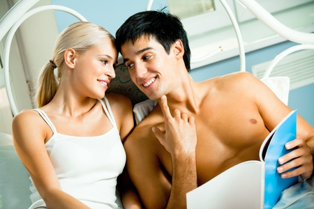 Young happy smiling couple reading magazine together at bedroom photo