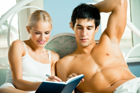 Young attractive happy smiling couple with notebook or organizer at home photo