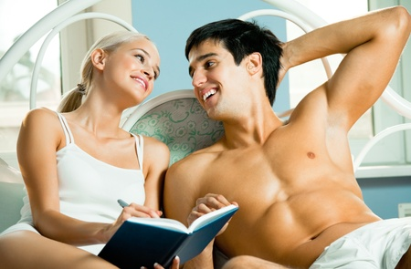 Young attractive happy smiling couple with notebook or organizer at home Stock Photo - 8629892