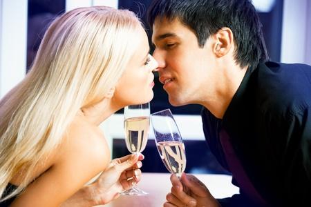 enamorados besandose: Parte de la joven pareja amorosa feliz con champ�n bes�ndose en Foto de archivo