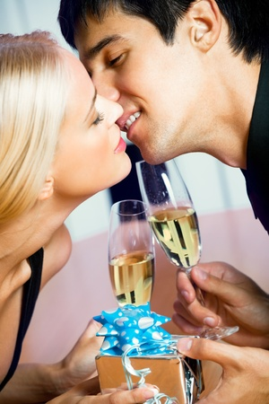Young happy amorous couple with champagne and gift, kissing at party photo