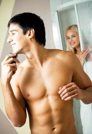 couple bathroom: Shaving man and young woman at bathroom