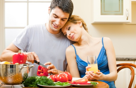 Young happy smiling amorous couple cooking together at home Stock Photo - 8697455