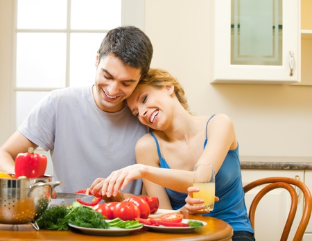 Young happy smiling amorous couple cooking together at home photo