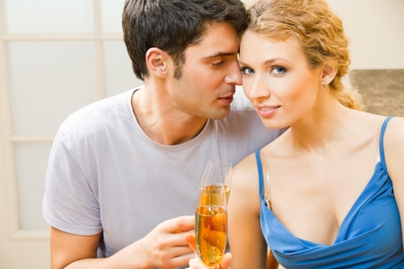 Young happy amorous couple celebrating with champagne at home Stock Photo - 8697463