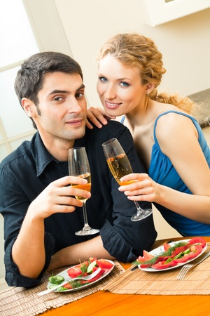 Young happy amorous couple celebrating with champagne at home photo