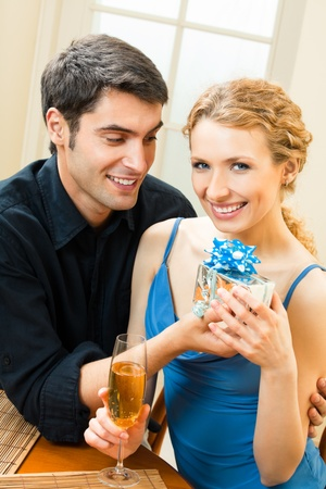 Young happy smiling amorous couple with gift and champagne at home Stock Photo - 8697460