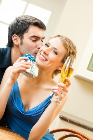 Young happy smiling amorous couple with gift and champagne at home Stock Photo - 8697469