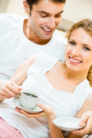 Young happy amorous couple drinking coffee together at home photo