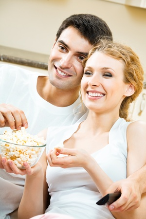 Young happy smiling couple eating popcorn and watching TV together at home photo