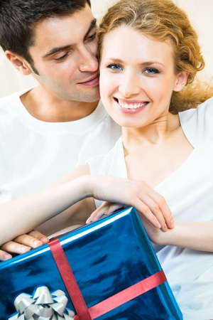 amorous: Young happy smiling amorous couple with gift at home