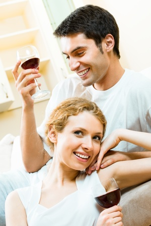 Young happy amorous couple with redwine at home photo