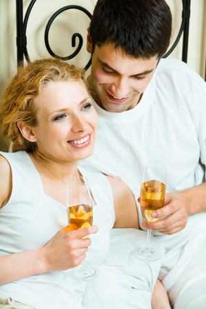 Young happy amorous couple celebrating with champagne at bedroom photo