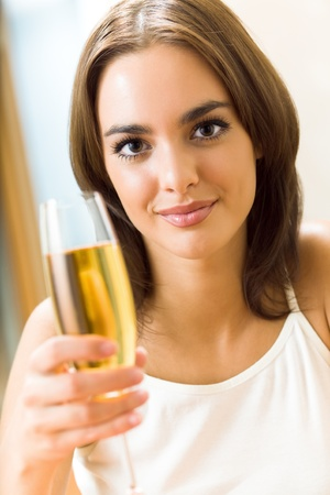 Portrait of young happy smiling woman with glass of champagne, at home photo