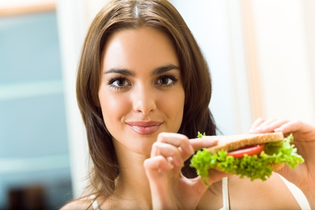 Portrait of young happy smiling woman with sandwich at home
