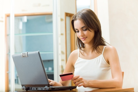 internet shopping: Young happy smiling woman paying by plastic card, at home