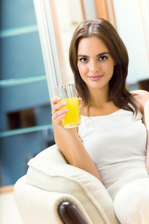 Young woman with orange juice at home photo