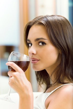 woman drinking wine: Portrait of young woman with glass of red wine, at home