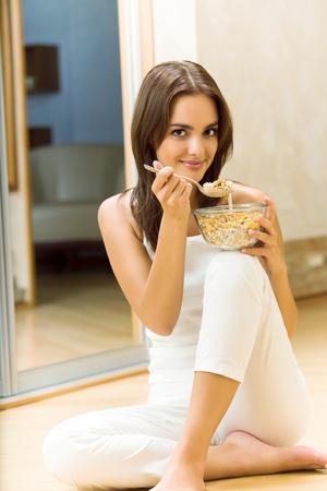 muslin: Young woman eating cereal muslin at home Stock Photo