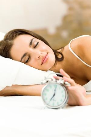 um jovem mulher só: Jovem mulher com despertador na cama em manh Imagens