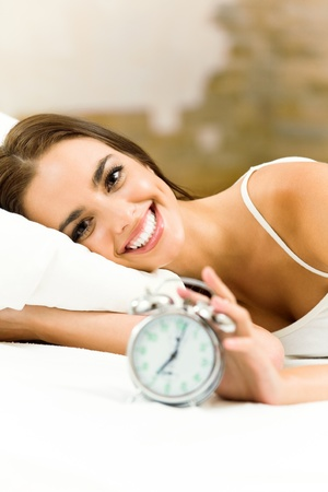 Young woman with alarmclock on the bed at the morning photo