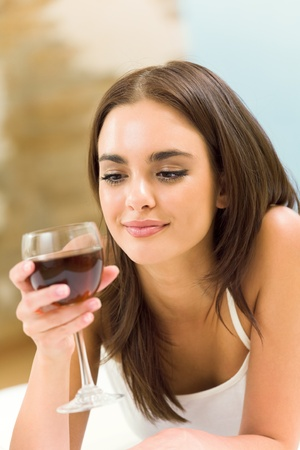 woman drinking wine: Portrait of young woman with glass of red wine, on bed