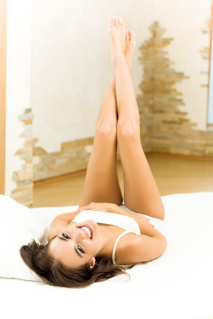 lazyness: Young happy smiling woman waking up at bedroom