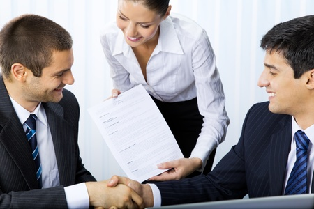 Three businesspeople handshaking with document at office  photo