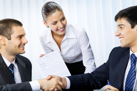 signing contract: Three businesspeople handshaking with document at office