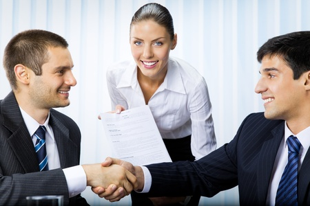 Three businesspeople handshaking with document at office Stock Photo - 8773232