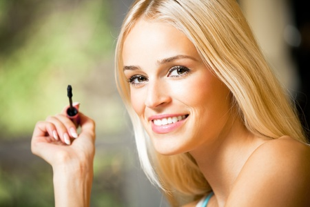 Portrait of young smiling woman applying mascara photo