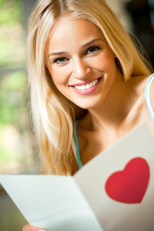 Young happy smiling woman, reading valentine card at home photo