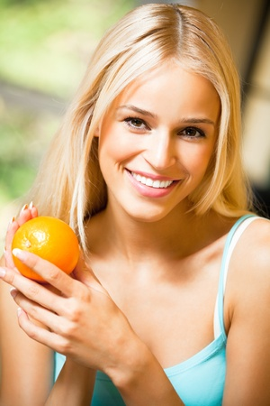 Portrait of young smiling woman with orange at home Stock Photo - 8773360