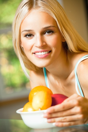 Young happy smiling woman with plate of fruits, indoors photo