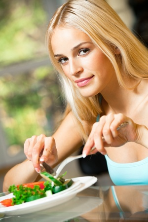 european food: Portrait of young happy smiling woman eating salad at home