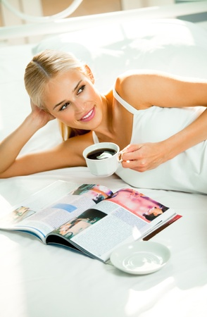 reading magazine: Young smiling woman reading magazine at home. All photos in magazine are mine.