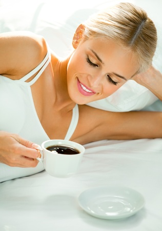 Young happy smiling woman with coffee, on bed photo