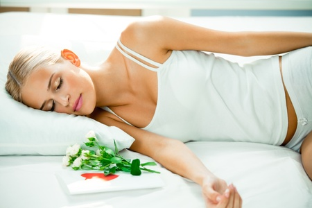 Portrait of young beautiful sleeping woman on bed with greeting valentines card and flowers photo