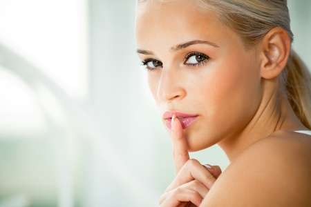quiet adult: Portrait of young woman with finger on lips, at home Stock Photo