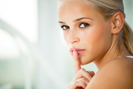 quiet adult: Ritratto di giovane donna con il dito sulle labbra, a casa